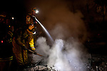 SAN BRUNO, CA - SEPTEMBER 9: Firefighters mop-up after a fire September 9, 2010 in a San Bruno, California residential street. A massive explosion rocked a neighborhood near San Francisco International Airport.