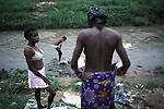 KINSHASA, DEMOCRATIC REPUBLIC OF CONGO - APRIL 29: Esther Yandakwa (c), age 9, takes bath in a river with her friends Francine Nyanda, age 14, and Gladys Lutadila, age 14, on April 29, 2006 in Matonge district in central Kinshasa Congo, DRC. Esther is homeless and works as a prostitute together with four fourteen-year-old friends. They live outside next to a polluted river. She's been three years on the street and has run away from her family. She has from time to time been living in a homeless shelter for children, but doesn?t like the rules there. She usually smokes cigarettes, marijuana, drinks whiskey and sometimes takes Valium. She charges the clients as little as US$ 1. About 15,000 children are estimated to live on the streets of Kinshasa. Congo, DRC is in ruins after forty years of mismanagement by the corrupt dictator and former president Mobuto Sese Seko. He fled the country in 1997 and a civil war started. The country is planning to hold general elections by July 2006, the first democratic elections in forty years.(Photo by Per-Anders Pettersson)
