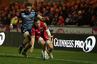 Steffan Evans of the Scarlets (R) grabs the ball from the ground while closely followed by Alex Cuthbert of Cardiff Blues during the Guinness PRO14 match between Scarlets and Cardiff Blues at Parc Y Scarlets Stadium, Llanelli, Wales, UK. Saturday 28 October 2017