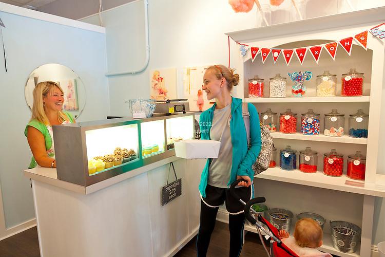 Sugar Sugar in Salem, Oregon.  Proprietor Dana Heuberger selling cupcakes to a customer in the store.