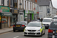 "Pictured: Police outside the Lloyds Bank on the High Street of Gorseinon, Wales, UK. Tuesday 20 November 2018<br /> Re: Two men with machetes are being hunted by police after trying to rob a Lloyds Bank in Gorseinon, near Swansea.<br /> Armed officers, police dogs and helicopter responded to the armed robbery at 10:00am on Tuesday.<br /> According to witnesses reports, the robbers ""came through the ceiling"" and held a member of staff by the throat.<br /> South Wales Police said nobody was hurt during the incident.<br /> A witness said: ""They had a girl from Lloyds by the throat. After robbing the bank they used a car to drive off."""