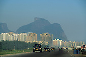 Barra da Tijuca, Rio de Janeiro, Brazil. High-rise appartment blocks and cars driving on a wide road.