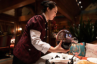 China - Beijing - A waitress serving red wine at East Wine Cellar, a reputed restaurant with a cellar hosting more than 10,000 bottles of top international and Chinese wines.<br />