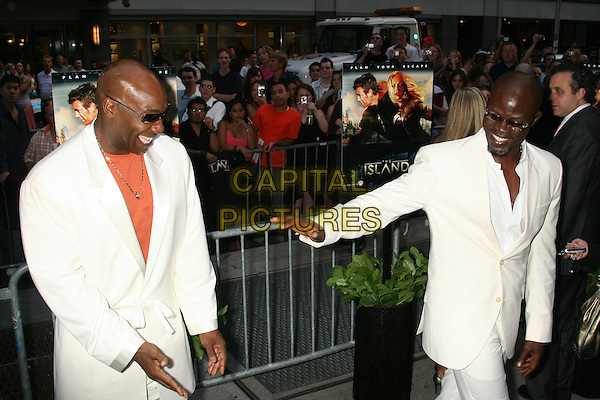 """MICHAEL CLARKE DUNCAN & DJIMON HOUNSOU.At """"The Island"""" New York Film Premiere, .held at  Ziegfeld Theatre in New York City, .New York, USA, 7th July 2005..full length clark white suits hand gesture.Ref: IW.www.capitalpictures.com.sales@capitalpictures.com.©Ian Wilson/Capital Pictures."""