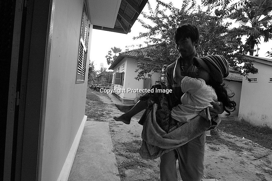 Health center Cambodia . A man is carrying his young wife into a quiet room. In Cambodia, it is the husbands that must clean the delivery room and burn the placenta. This practise began a few years ago  for the sake of hygiene. Before, the custom was to bring the placenta home and keep it for several weeks besides the new born baby. Trapeng Andeuk, Takeo province, Cambodia-2009