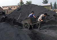 Two workers convey coal as fuel in a brickkiln in Bazhou, Hebei province, China..04-SEP-04