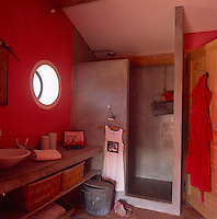 A red bathroom with a concrete shower area. A porthole window is set in the wall above a washbasin placed on a concrete shelf with wicker baskets below.
