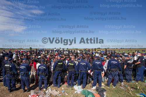 Line of police officers stand guard at a collection point of illegal migrants near Roszke (about 174 km South of capital city Budapest), Hungary on September 07, 2015. ATTILA VOLGYI
