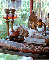 Oil lamps and storm lanterns are used for reading and to illuminate a collection of skulls and objects on this rustic table