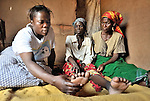 Home Based Care worker Maria Silo (left) with patient Sellah Mwanza in Ekwendeni, Malawi. Silo is HIV positive, and on antiretrovirals, as is her husband, but their five children are all HIV negative because she got into the Prevention of Mother to Child Transmission program. Since starting antiretrovirals, Silo reports she is feeling better.