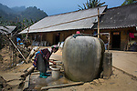 Ethnic Hmong woman fetching water from a storage barrel, Sapa, Vietnam