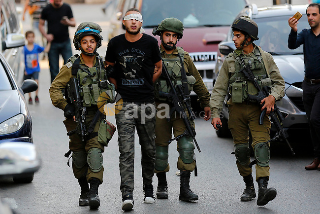 Israeli security forces detain a Palestinian youth after soldiers entered an area controlled by the Palestinian authority in the divided city of Hebron, in the Israeli-occupied West Bank, on September 20, 2017. Photo by Wisam Hashlamoun