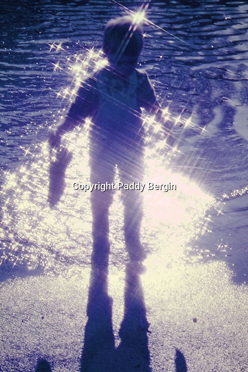 Reflection of boy silhouetted by sunlight. Paddling in water with Wellingtons on.<br />