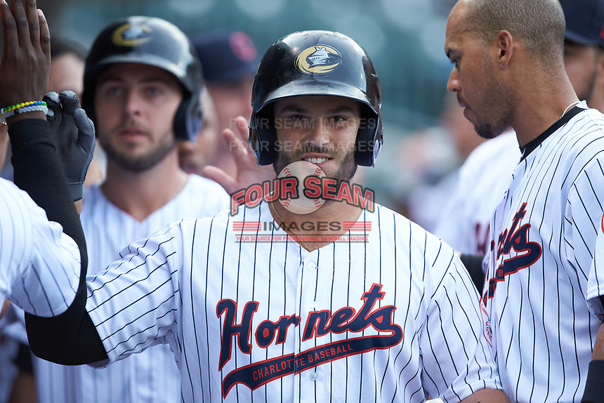 Daniel Palka (7) of the Charlotte Hornets is congratulated by his teammates after hitting a home run against the Louisville Bats at BB&T BallPark on June 22, 2019 in Charlotte, North Carolina. The Hornets defeated the Bats 7-6. (Brian Westerholt/Four Seam Images)