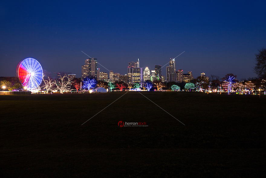 The Trail of Lights and Ferris wheel on display at Zilker Park surrounded by the majestic downtown Austin Skyline. Zilker Park is Austin's main hub for all year round events from Kite Festivals to the country's largest music festivals, concerts and sporting events.