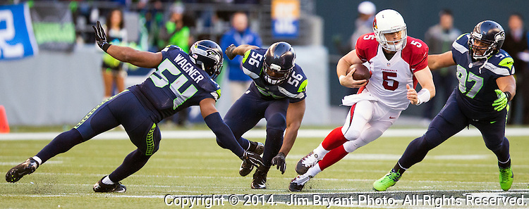Arizona Cardinals quarterback Drew Stanton (5) scrambles away from Seattle Seahawks defensive end Cliff Avril (56), linebacker Bobby Wagner (54) and defensive tackle Jordan Hill (97) at CenturyLink Field in Seattle, Washington on November 23, 2014. Stanton completed 14 of 26 passes for 149 yards and had one interception in the Cardinals 3-19 loss to the Seahawks.     ©2014. Jim Bryant Photo. All Rights Reserved.
