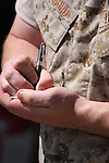 A young modern military man as a soldier in the United States army signing a sheet a paper with a pen
