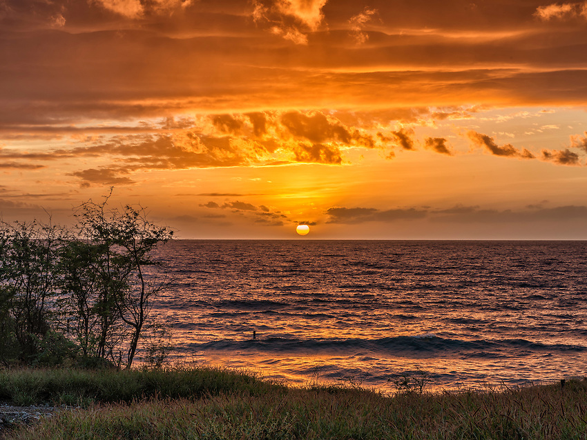 View of a sunset from the southwest coast of Maui at Kamaole Park, Kihei.