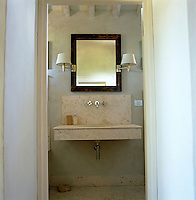 A stone wash basin glimpsed through the open door to a bathroom