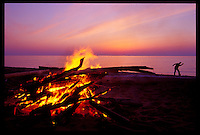 A CAMPFIRE BURNS ON A LAKE SUPERIOR BEACH IN ONTONAGON MICHIGAN AT DUSK AS A SILHOUETTED MAN SKIPS STONES.