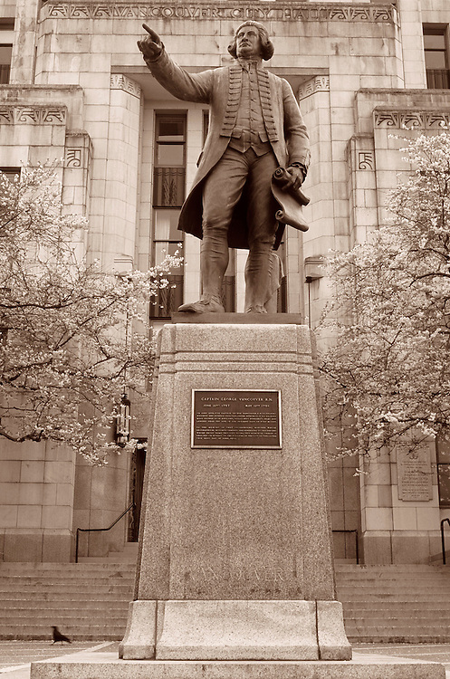Statue of Captain George Vancouver by Charles Marega, with crow and Spring cherry blossoms, City Hall, Vancouver, BC.