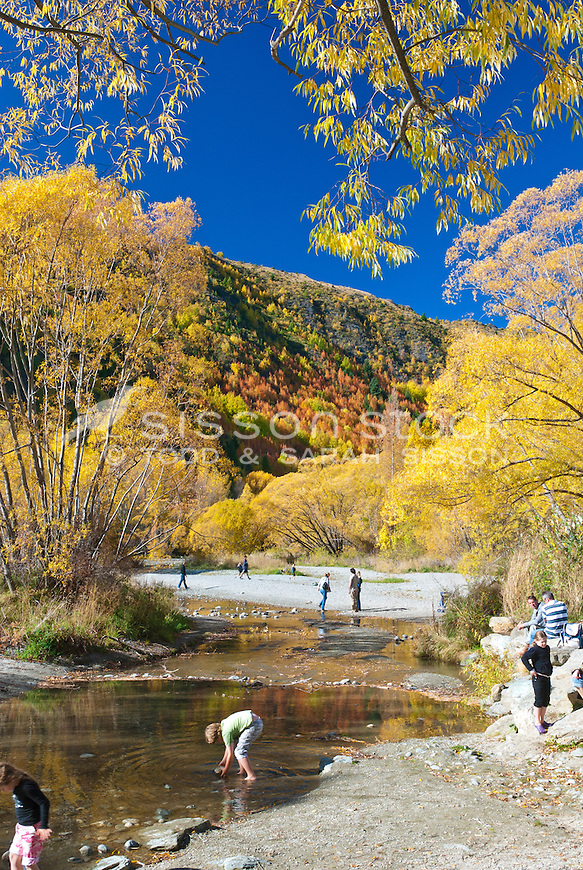 People relaxing next to the Arrow River in Autumn, Arrowtown, Central Otago, South Island, New Zealand