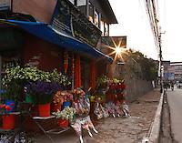 The sun rises over a flower shop on a Kathmandu Street.