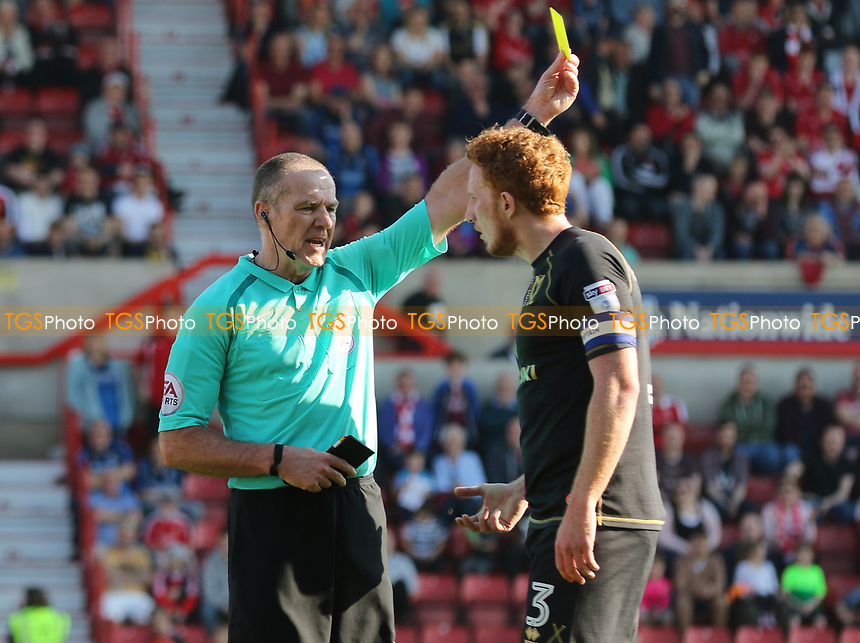 Referee Graham Salisbury issues a yellow card to Dean Lewington during Swindon Town vs MK Dons, Sky Bet EFL League 1 Football at the County Ground on 8th April 2017