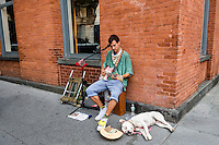New York, NY 8 August 2015 - A street performer with a white pit bull dog on Prince Street in the Soho neighbourhood of Manhattan.