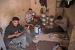 Young men metal workers in small room in the medina, Marrakech, Morocco, north Africa