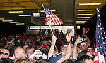 12 June 2006: A U.S. fan waives a flag at a crowded train station as fans wait for transport to the stadium. The United States played the Czech Republic at Veltins Arena in Gelsenkirchen, Germany in match 10, a Group E first round game, of the 2006 FIFA World Cup.