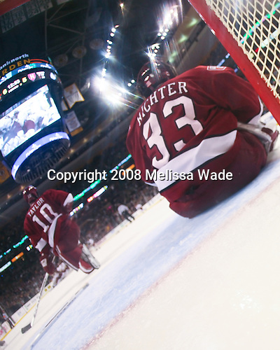 Mike Taylor (Harvard 10) and Kyle Richter (Harvard 33) take a moment as the pile of celebrating BC players can be seen on the scoreboard. The Boston College Eagles defeated the Harvard University Crimson 6-5 in overtime on Monday, February 11, 2008, to win the 2008 Beanpot at the TD Banknorth Garden in Boston, Massachusetts.