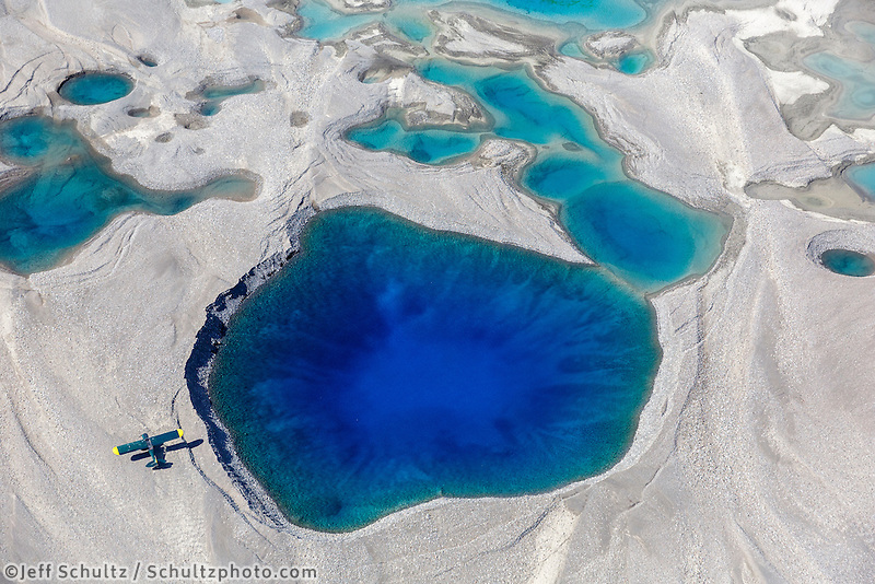Super Cub airplane sits next to a blue pool of water at the foot of Barnard Glacier.   Jeff Schultz Photo workshop via Alaska Photo Treks at Ultima Thule Lodge in the Wrangell St. Elias National Park    Summer  Alaska<br />