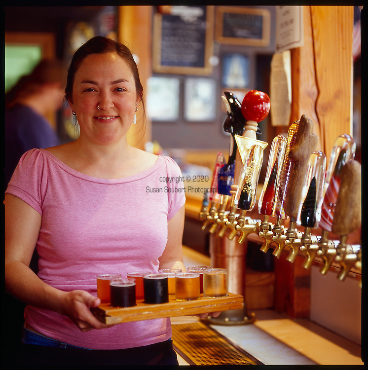 A waitress serves up a round of tasters, small glasses of a variety of beers made on the premises
