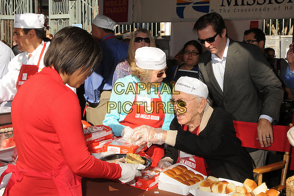 Anne Douglas, Kirk Douglas.Los Angeles Mission Thanksgiving Dinner 2012 held at the LA Mission, Los Angeles, California, USA..November 21st, 2012.half length blue black white red apron hat sunglasses shades married husband wife food profile.CAP/ADM/BP.©Byron Purvis/AdMedia/Capital Pictures.