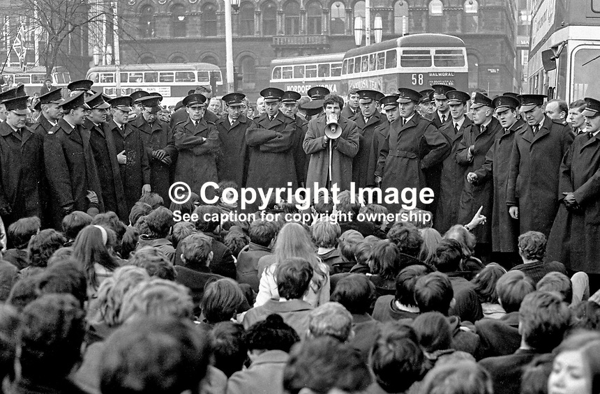 Student sit-down in Donegall Square East, Belfast, N Ireland, as part of the civil rights campaign, the precursor to the N Ireland Troubles. The guy with microphone is Kevin Boyle, who went on to become a university law lecturer. Ref: Student_sit-down_CRA_Campaign_196810160240a.<br />