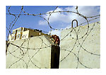 A Palestinian man tries to cross the wall built to separate the Palestinian territories from Israel, June 1,2003, in the West Bank neighbourhood of Abu Dis, next to Jerusalem. Photo by Quique Kierszenbaum