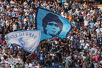 Napoli's supporters hold up a flag with a portrait of former Napoli player and football legend Diego Armando Maradona as celebrate after winning an Italian Serie A football match against Siena and qualify for the UEFA Champions League on May 12, 2013 at San Paolo Stadium in NaplesNAPOLI CACIO FESTA QUALIFICAZIONE  CHAMPIONS