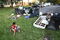 A young boy sits on the grass beside a pile of discarded things outside a foreclosed home in Manassas, Virginia. The area is suffering from a major collapse in the housing market following the subprime crisis and global credit crunch, which has forced the foreclosure and abandonment of numerous properties...