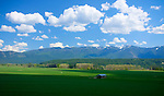 Idaho, North, Boundary County, Bonners Ferry.  A barn and spring landscape in the Kootenai River Valley with the Cabinet Mountains distant.