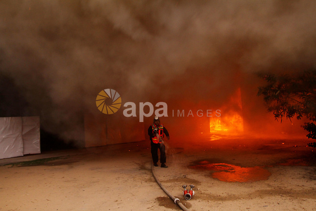 Palestinian fire fighters try to extinguish a fire at a workshop for woodwork in Gaza City November 14, 2011. The cause of the fire is unclear. Photo by Ashraf Amra