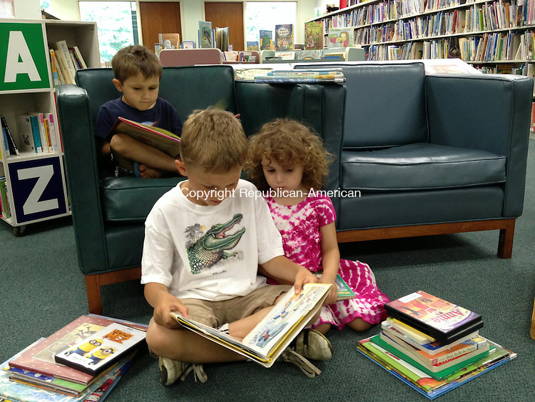 MIDDLEBURY, CT - 25 June 2014: 062514BB01 --- Melissa Parisi's children spend some time at Middlebury Public Library Wednesday. Jai, 5, curls up in a chair with a book as his brother, Julian, 8, reads a story to their sister, Jolan, 4. Bill Bittar Republican-American