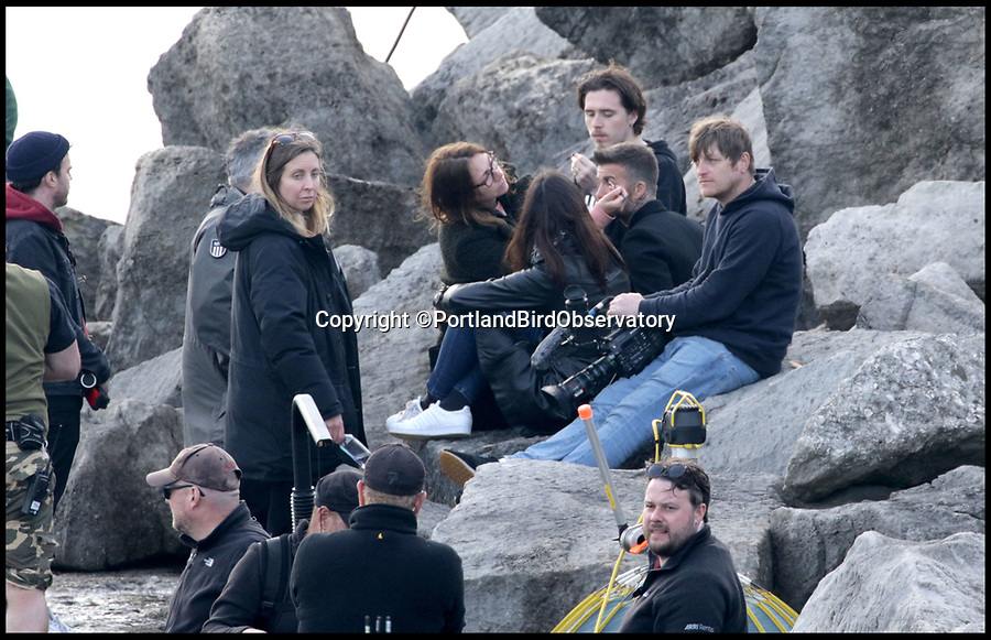 BNPS.co.uk (01202 558833)Pic:   PortlandBirdObservatory/BNPS<br /> <br /> David Beckham's oldeset son Brooklyn (top, behind David), joined him on the shoot.<br /> <br /> David Beckham lets off some steam as he records a new TV advert for his own skincare product range on a windswept rock.<br /> <br /> The former England footballer was seen filming at the tip of the Isle of Portland in Dorset last night (Tues).<br /> <br /> His production team used canisters of smoke to give the ad more of a wild, atmospheric theme.