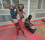 A girl feeds her sibling as part of a supplemental feeding program for malnourished children and mothers run by the clinic of the Loreto School in Rumbek, South Sudan. The school is run by the Institute for the Blessed Virgin Mary--the Loreto Sisters--of Ireland. Behind them, their mother shells peanuts that are used in the preparation of the food.