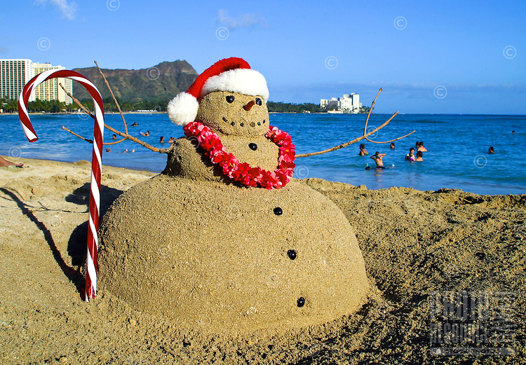 Santa sandman with candycane, lei and santa cap on Waikiki beach with Diamond head, Oahu