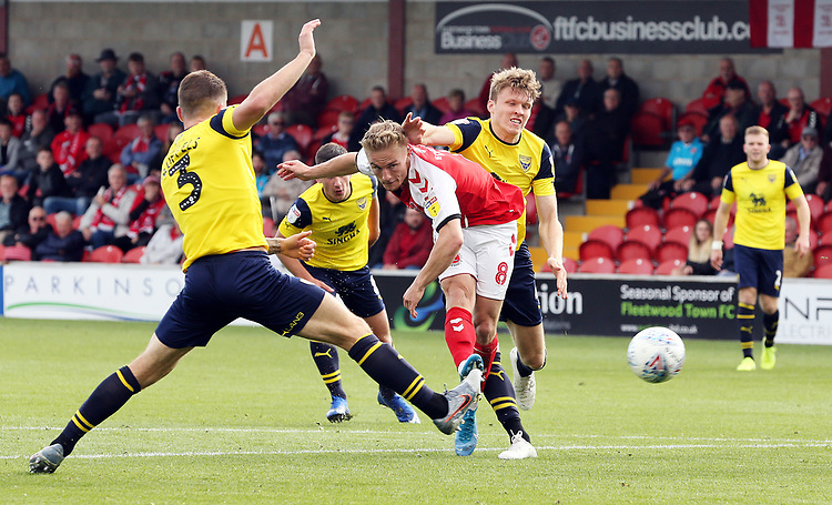 Fleetwood Town's Kyle Dempsey shoots despite the attentions of Oxford United's Josh Ruffels (left) and Rob Dickie<br /> <br /> Photographer Rich Linley/CameraSport<br /> <br /> The EFL Sky Bet League One - Fleetwood Town v Oxford United - Saturday 7th September 2019 - Highbury Stadium - Fleetwood<br /> <br /> World Copyright © 2019 CameraSport. All rights reserved. 43 Linden Ave. Countesthorpe. Leicester. England. LE8 5PG - Tel: +44 (0) 116 277 4147 - admin@camerasport.com - www.camerasport.com