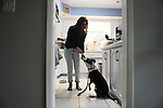 Allison Ziema, 25, with her family's dog Wilson in the kitchen of her family's house in Wilmette, Illinois on April 22, 2015.  Ziema, a multimedia photojournalist, lives at home with her brother Brian, 29, a paramedic hoping to join the Chicago Fire Department, and their parents.