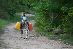 A boy rides a donkey carrying water in Picmy, a village on the Haitian island of La Gonave, where Service Chrétien d'Haïti has helped survivors of the massive 2016 Hurricane Matthew. SCH is a member of the ACT Alliance, and providing donkeys to affected families has been a common practice, as the animals make it easier to move cops to market, fetch water, and their owners can sell the offspring for a profit.