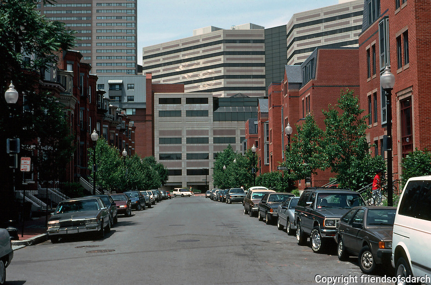 Boston:  Back Bay--Yarmouth St. looking east from Columbus, Copley  Place--low-cost housing--looming behind. Bow windows left; new compatible housing , right--and rap music coming from apartments.  Photo '91.