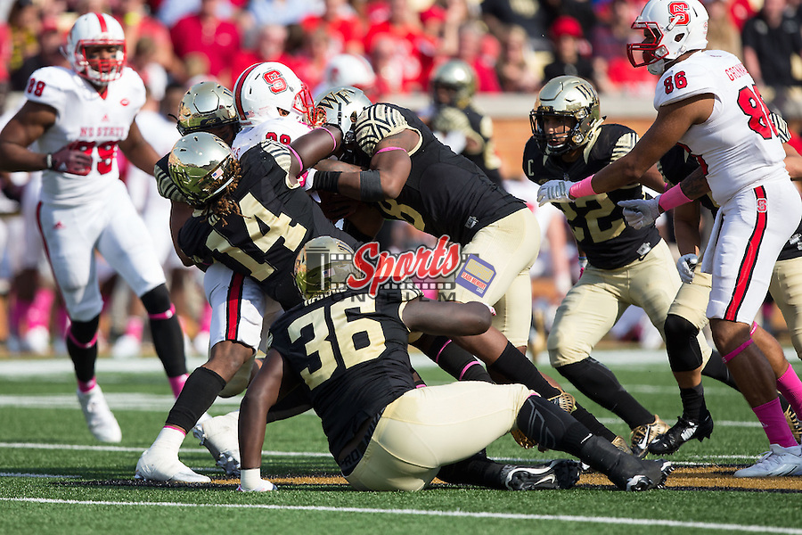 Jaylen Samuels (28) of the North Carolina State Wolfpack is tackled by Wendell Dunn (14), Marquel Lee (8) and Tylor Harris (36) of the Wake Forest Demon Deacons during second half action at BB&T Field on October 24, 2015 in Winston-Salem, North Carolina.  The Wolfpack defeated the Demon Deacons 35-17.   (Brian Westerholt/Sports On Film)